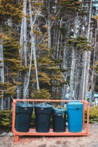 blue plastic trash bins on forest during daytime
